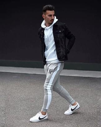 Cómo combinar: tenis de cuero blancos, pantalón de chándal gris, sudadera con capucha blanca, chaqueta vaquera negra