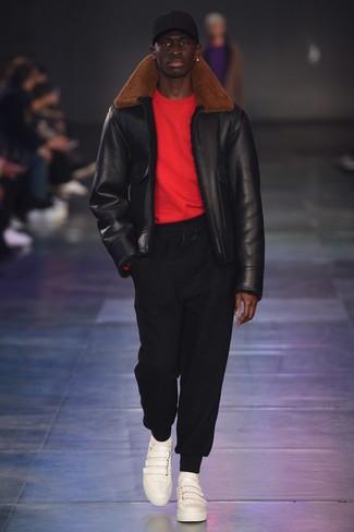 Cómo combinar: tenis de cuero blancos, pantalón de chándal negro, jersey con cuello circular rojo, chaqueta de piel de oveja negra