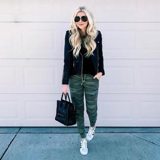 Cómo combinar: tenis de cuero en blanco y negro, pantalón de chándal de camuflaje verde oscuro, jersey con cuello circular negro, chaqueta motera de cuero negra