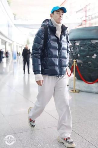 Cómo combinar: deportivas grises, pantalón de chándal blanco, jersey de cuello alto de punto blanco, plumífero azul marino