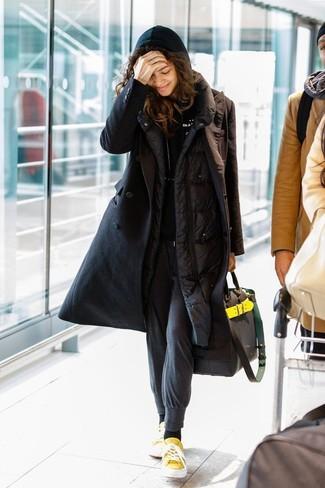 Cómo combinar: tenis de lona amarillos, pantalón de chándal en gris oscuro, sudadera con capucha negra, abrigo de plumón negro