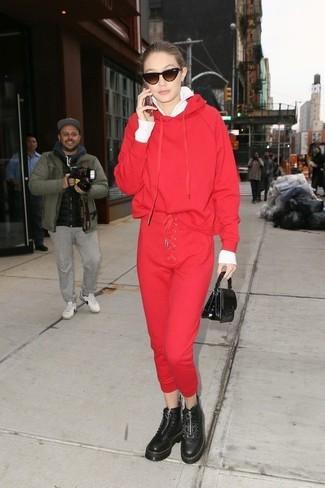 Cómo combinar: botas planas con cordones de cuero gruesas negras, pantalón de chándal rojo, sudadera con capucha roja, jersey con cremallera blanco