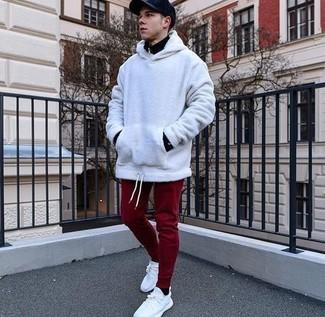 Cómo combinar: tenis de lona blancos, pantalón de chándal burdeos, sudadera con capucha blanca, jersey de cuello alto con cremallera negro