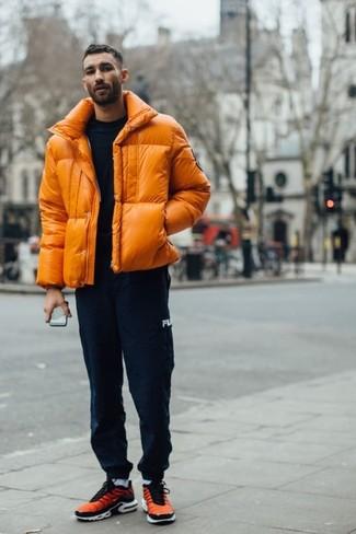 Outfits hombres: Utiliza un plumífero naranja y un pantalón de chándal azul marino para una apariencia fácil de vestir para todos los días. Deportivas naranjas añadirán un nuevo toque a un estilo que de lo contrario es clásico.