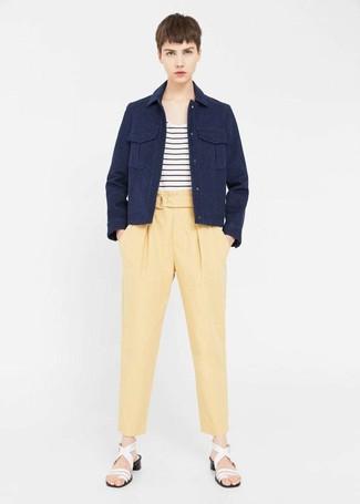 Cómo combinar: sandalias de tacón de cuero blancas, pantalón de pinzas amarillo, camiseta con cuello circular de rayas horizontales en blanco y negro, chaqueta militar azul marino