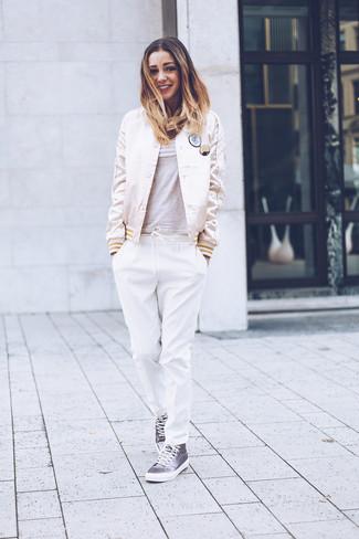 Cómo combinar: zapatillas altas de lona grises, pantalón de pinzas blanco, camiseta con cuello circular gris, cazadora de aviador de satén en beige
