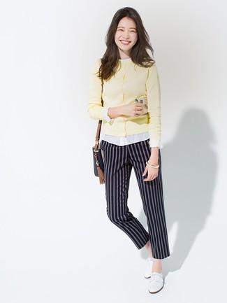 Cómo combinar: zapatos oxford de cuero blancos, pantalón de pinzas de rayas verticales azul marino, blusa de botones blanca, cárdigan amarillo