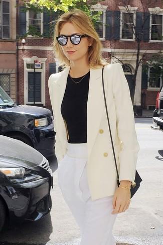 Cómo combinar: bolso bandolera de cuero negro, pantalón de pinzas blanco, camiseta con cuello circular negra, blazer cruzado blanco