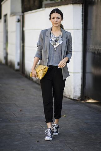 Cómo combinar: tenis de lona en negro y blanco, pantalón de pinzas negro, camiseta con cuello circular gris, blazer gris