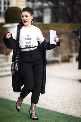 Cómo combinar: zapatos de tacón de ante en negro y blanco, pantalón de pinzas negro, camiseta con cuello circular estampada en blanco y negro, gabardina negra