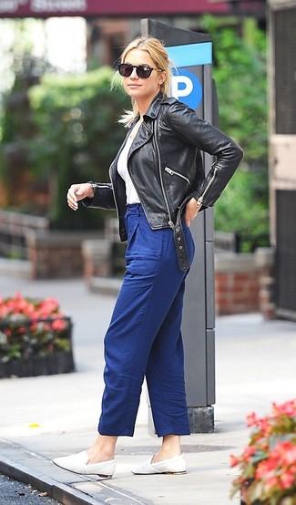 Cómo combinar: mocasín de cuero blancos, pantalón de pinzas azul, camiseta con cuello en v blanca, chaqueta motera de cuero negra