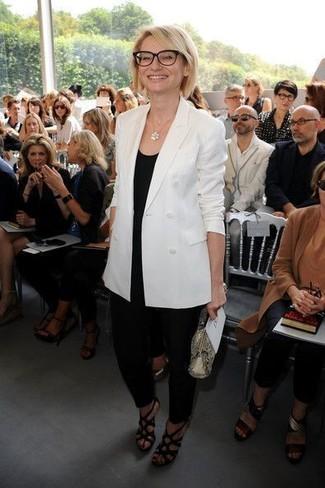 Cómo combinar: sandalias de tacón de cuero negras, pantalón de pinzas negro, camiseta sin manga negra, blazer cruzado blanco