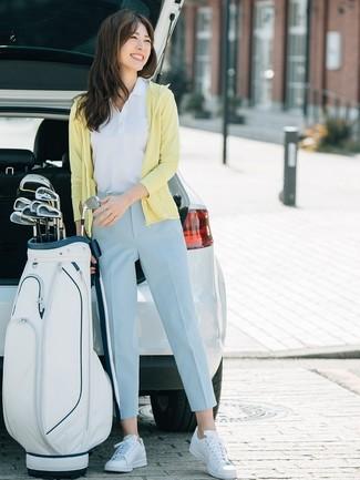 Cómo combinar: tenis de cuero blancos, pantalón de pinzas celeste, camisa polo blanca, sudadera con capucha amarilla