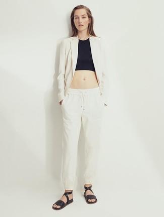 Cómo combinar: sandalias planas de cuero negras, pantalón de pinzas de lino en beige, top corto negro, blazer de lino en beige