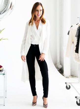 Cómo combinar: zapatos de tacón de ante bordados negros, pantalón de pinzas negro, blusa sin mangas blanca, abrigo duster blanco