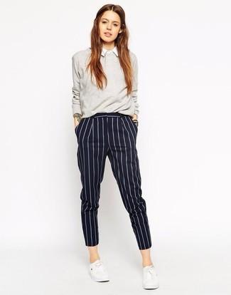 Combinar un pantalón de vestir de rayas verticales azul marino: Para seguir las tendencias usa un jersey con cuello circular gris y un pantalón de vestir de rayas verticales azul marino. Tenis blancos añadirán un nuevo toque a un estilo que de lo contrario es clásico.