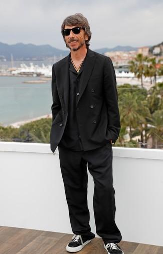 Cómo combinar: tenis de lona en negro y blanco, pantalón de vestir negro, camisa de manga larga negra, blazer cruzado negro