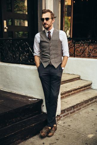 Cómo combinar: zapatos brogue de cuero en marrón oscuro, pantalón de vestir azul marino, camisa de manga larga de rayas verticales blanca, chaleco de vestir de lana marrón