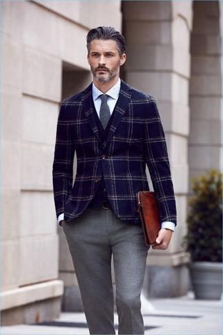 Cómo combinar: bolso con cremallera de cuero en tabaco, pantalón de vestir de lana gris, camisa de vestir a lunares blanca, blazer de lana de tartán azul marino