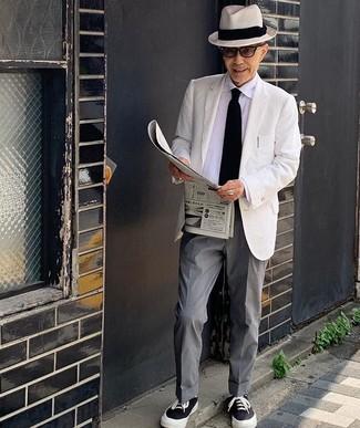 Combinar una corbata de punto negra: Ponte un blazer blanco y una corbata de punto negra para rebosar clase y sofisticación. Si no quieres vestir totalmente formal, elige un par de tenis de lona en negro y blanco.