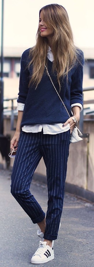 Combinar un pantalón de vestir de rayas verticales azul marino: Considera emparejar un jersey de pico azul marino con un pantalón de vestir de rayas verticales azul marino para cualquier sorpresa que haya en el día. Tenis blancos añadirán interés a un estilo clásico.