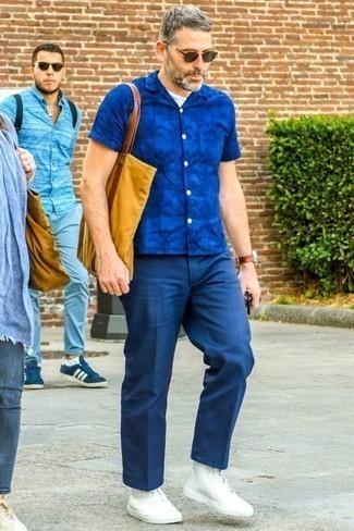 Outfits hombres: Empareja una camisa de manga corta estampada azul junto a un pantalón de vestir azul marino para lograr un look de vestir pero no muy formal. ¿Quieres elegir un zapato informal? Usa un par de zapatillas altas de lona blancas para el día.