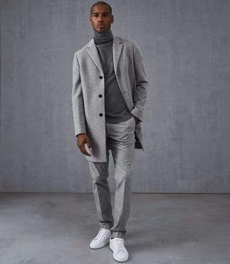 Outfits hombres: Intenta ponerse un abrigo largo gris y un pantalón de vestir de lana gris para un perfil clásico y refinado. Si no quieres vestir totalmente formal, completa tu atuendo con tenis de cuero blancos.