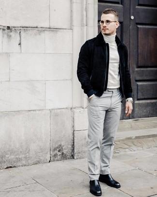 Cómo combinar: botines chelsea de cuero negros, pantalón de vestir gris, jersey de cuello alto blanco, cazadora de aviador de ante azul marino