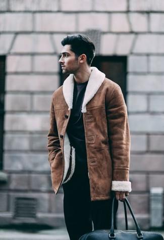 Cómo combinar: bolsa de viaje de cuero negra, pantalón de vestir negro, sudadera negra, chaqueta de piel de oveja marrón
