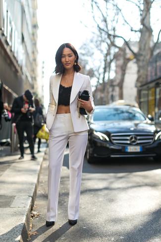 Cómo combinar: zapatos de tacón de ante con adornos negros, pantalón de vestir blanco, top corto de encaje negro, blazer cruzado blanco