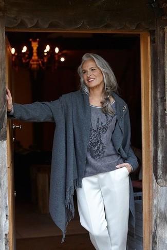 Cómo combinar: broche dorado, pantalones anchos blancos, jersey con cuello circular estampado en gris oscuro, abrigo en gris oscuro