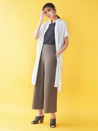 Cómo combinar: chinelas de cuero negras, pantalones anchos de punto marrónes, camiseta con cuello circular en gris oscuro, abrigo duster blanco