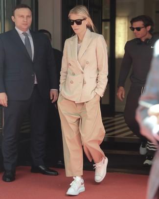 Cómo combinar: tenis de cuero blancos, pantalones anchos marrón claro, camiseta con cuello circular blanca, blazer cruzado en beige