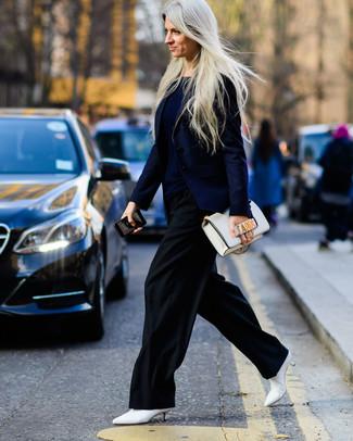 Cómo combinar: botines de cuero blancos, pantalones anchos negros, camiseta con cuello circular azul marino, blazer azul marino