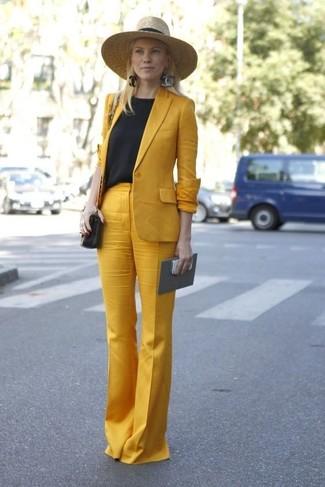 Cómo combinar: bolso bandolera de cuero negro, pantalones anchos mostaza, camiseta con cuello circular negra, blazer mostaza