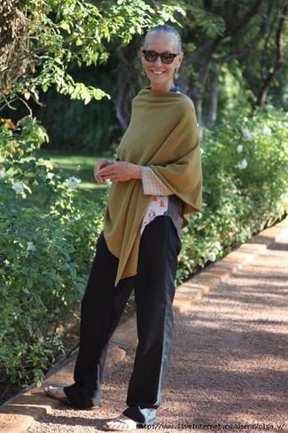 Cómo combinar: sandalias planas de cuero en beige, pantalones anchos negros, camiseta de manga larga estampada blanca, poncho verde oliva