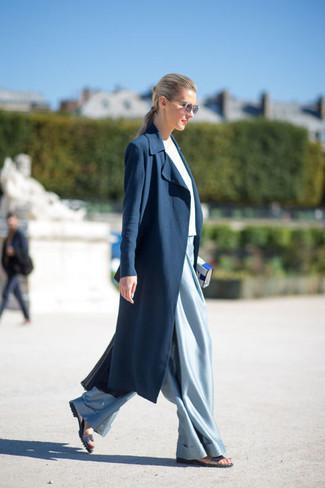 Cómo combinar: sandalias planas de cuero plateadas, pantalones anchos celestes, camiseta con cuello circular blanca, abrigo duster azul marino