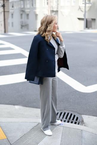 Cómo combinar: tenis de lona blancos, pantalones anchos grises, jersey de cuello alto gris, chaquetón azul marino