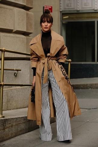 Cómo combinar: botines de cuero negros, pantalones anchos de rayas verticales en blanco y negro, jersey de cuello alto negro, gabardina marrón claro