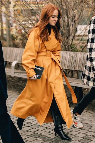 Cómo combinar: botines de cuero negros, pantalones anchos de cuero negros, jersey de cuello alto negro, gabardina de cuero naranja