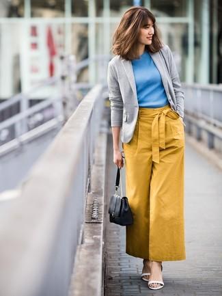Cómo combinar: sandalias de tacón de cuero blancas, pantalones anchos mostaza, jersey de manga corta azul, blazer de punto gris