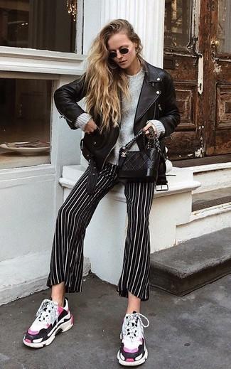 Cómo combinar: deportivas blancas, pantalones anchos de rayas verticales en negro y blanco, jersey oversized gris, chaqueta motera de cuero negra