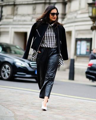Cómo combinar: zapatos de tacón de cuero blancos, pantalones anchos de cuero negros, blusa de manga larga a cuadros en negro y blanco, chaqueta motera de lana negra