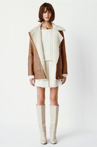 Cómo combinar: botas de caña alta de cuero en beige, pantalones cortos blancos, jersey de ochos blanco, abrigo de piel de oveja marrón
