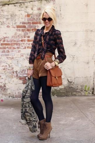 Cómo combinar: botines con cordones de cuero marrónes, pantalones cortos de ante marrónes, blusa de botones estampada negra, chaqueta motera de camuflaje verde