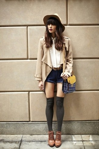 Cómo combinar: botines con cordones de cuero marrónes, pantalones cortos vaqueros azul marino, blusa de botones de seda blanca, gabardina marrón claro