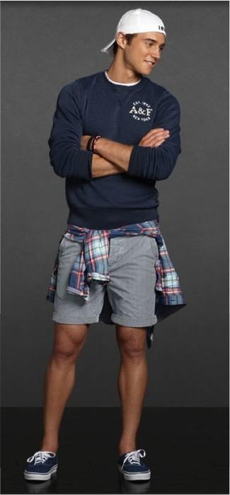 Cómo combinar: tenis azul marino, pantalones cortos grises, camisa de manga larga de tartán azul, jersey con cuello circular azul marino