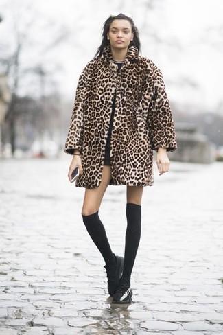 Cómo combinar: tenis de cuero negros, pantalones cortos negros, camiseta con cuello circular negra, abrigo de piel de leopardo marrón claro