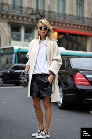 Cómo combinar: zapatillas slip-on de tartán grises, pantalones cortos de cuero negros, camiseta con cuello circular blanca, abrigo de forro polar en beige