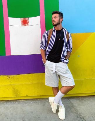 Cómo combinar: tenis blancos, pantalones cortos blancos, camiseta con cuello circular negra, camisa de manga larga de rayas verticales en blanco y azul